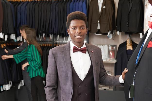 Hombre guapo en traje posando en boutique.
