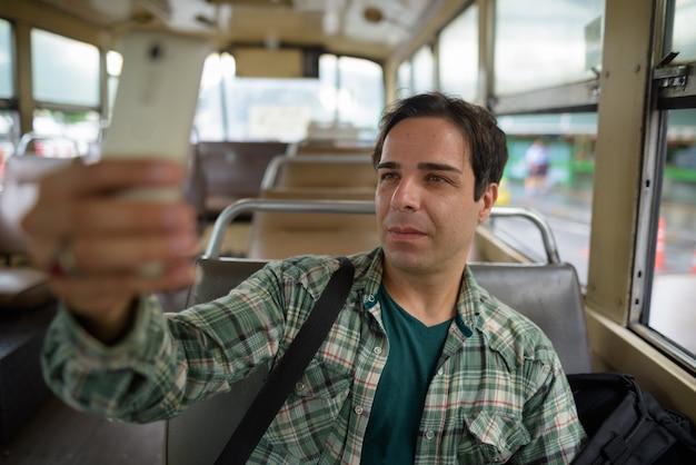 Hombre guapo turista persa sentado en el autobús y tomando selfie