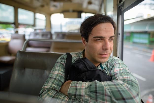Hombre guapo turista persa sentado en el autobús