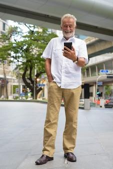 Hombre guapo turista senior explorando la ciudad de bangkok, tailandia