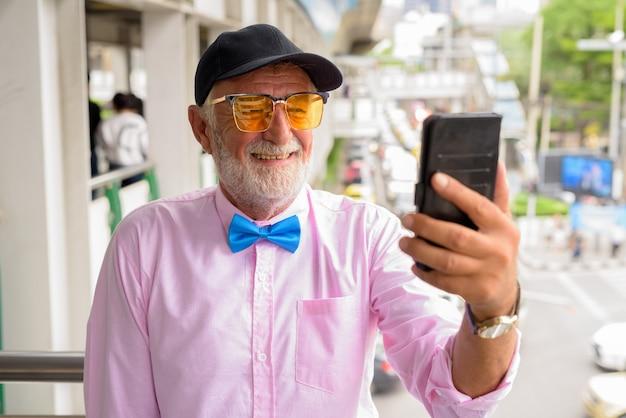 Hombre guapo turista senior explorando la ciudad de bangkok, thailandiaand