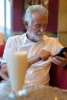Hombre guapo turista senior relajante dentro de la cafetería.