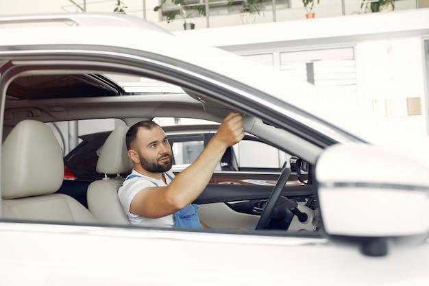 Hombre guapo en uniforme azul comprueba el coche