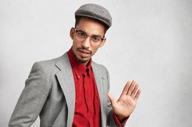Hombre guapo usa anteojos redondos, usa ropa pasada de moda, muestra la palma, intenta detener algo