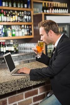Hombre guapo usando la computadora portátil y bebiendo una cerveza