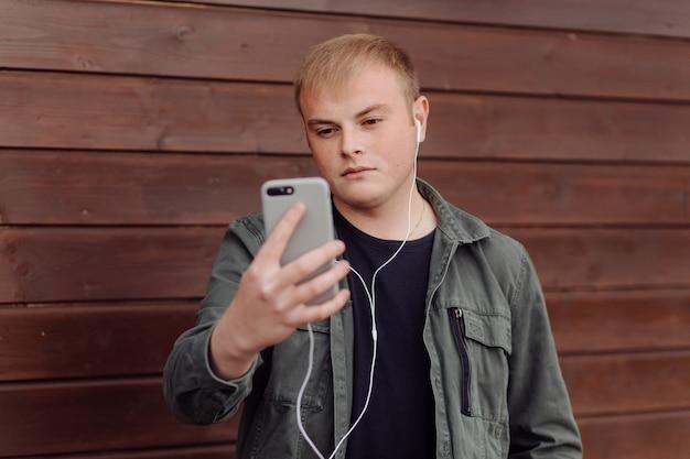 Hombre guapo está usando una computadora portátil y un teléfono al aire libre en la pared de madera