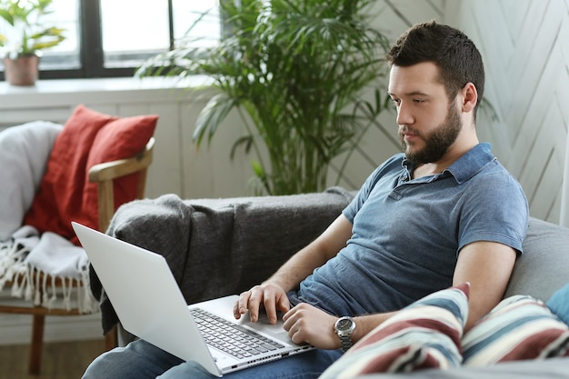 Hombre guapo usando laptop en casa. concepto de teletrabajo