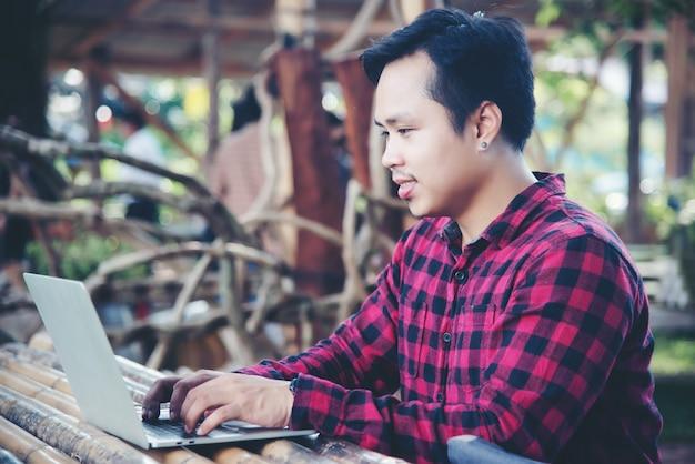 Hombre guapo usando laptop en la naturaleza de viaje