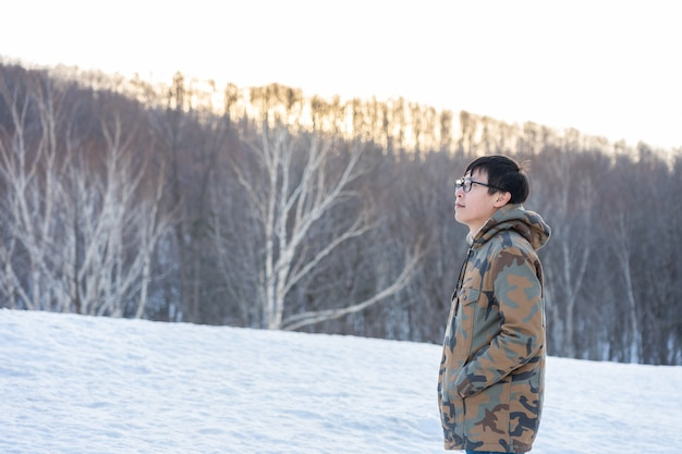 Hombre guapo vestido con frío, vestido con ropa de invierno, entre los pinos.
