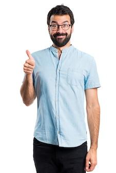 Hombre guapo con los vidrios azules con el pulgar para arriba