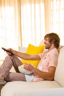 Hombre guapo viendo televisión y comiendo palomitas de maíz sentado en el sofá