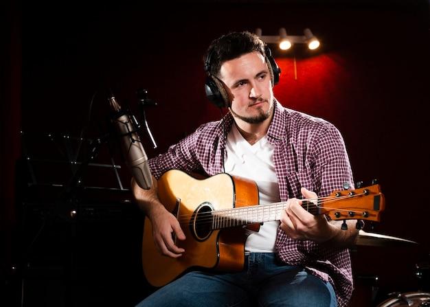 Hombre con guitarra acústica mirando a otro lado