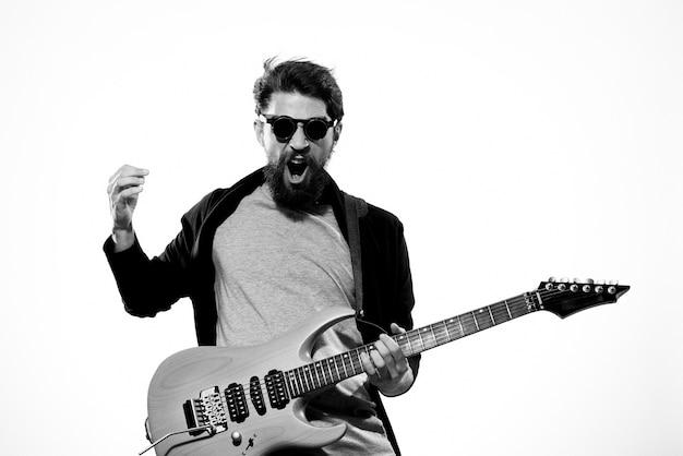 Hombre con guitarra en manos músico estrella de rock rendimiento estilo de vida fondo claro.