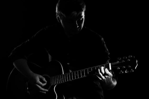Hombre con guitarra en la oscuridad