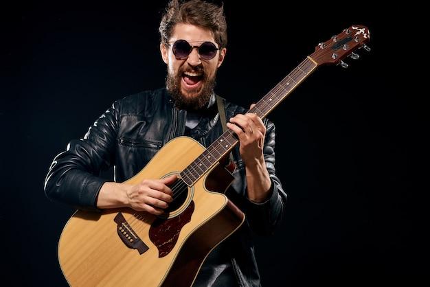 Hombre con una guitarra en sus manos, chaqueta de cuero negro, gafas de sol, música, emociones, negro