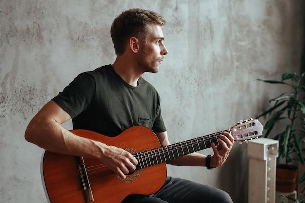 Hombre guitarrista tocando la guitarra en casa