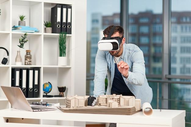 Hombre hábil como arquitecto revisando proyecto arquitectónico con gafas vr en la oficina moderna.