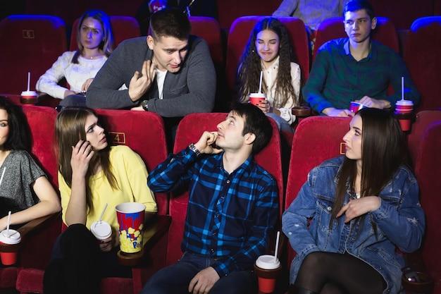Un hombre habla en voz alta por teléfono en una sala de cine y le impide ver una película. el hombre hace un comentario y le pide que apague el teléfono.