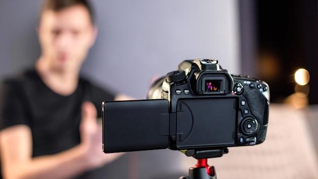 Hombre hablando a la cámara, grabándose a sí mismo en un vlog. trabajando desde casa. creador de contenido joven