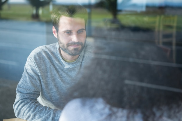 Hombre hablando con una mujer en la cafetería.
