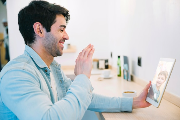 Hombre hablando con un niño pequeño usando tableta