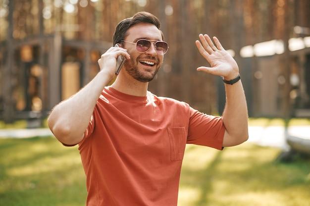 Hombre hablando por teléfono inteligente gesticulando afablemente
