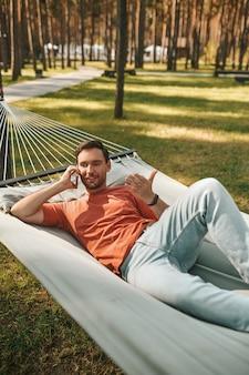 Hombre hablando por teléfono inteligente tumbado en una hamaca