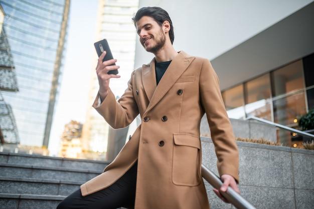 Hombre hablando por teléfono mientras baja una escalera