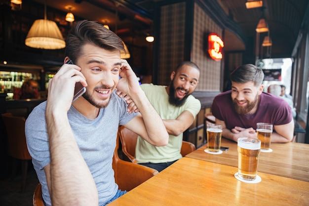 Hombre hablando por teléfono mientras sus amigos divertidos no le dejan hacerlo en el pub de cerveza