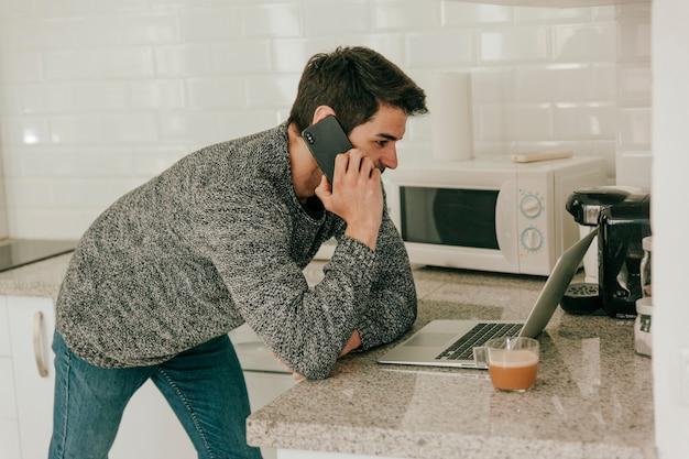 Hombre hablando por teléfono mientras usa la computadora portátil
