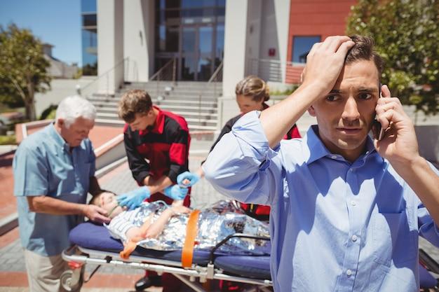 Hombre hablando por teléfono móvil y paramédicos examinando niño herido en segundo plano.