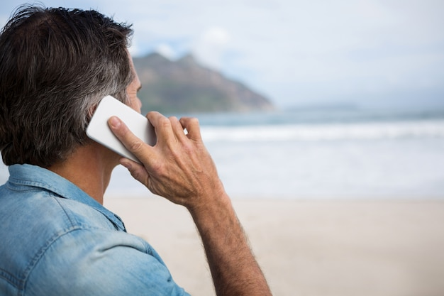 Hombre hablando por teléfono móvil en la playa