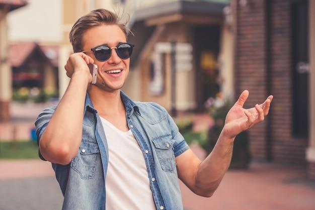El hombre está hablando por teléfono móvil y sonriendo