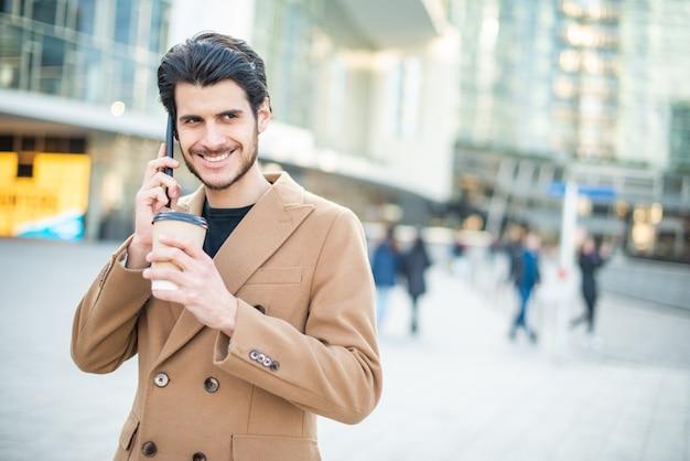 Hombre hablando por teléfono y sosteniendo una taza de café mientras camina en una ciudad