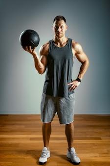 Un hombre hace ejercicios con un fitball sobre un fondo gris.