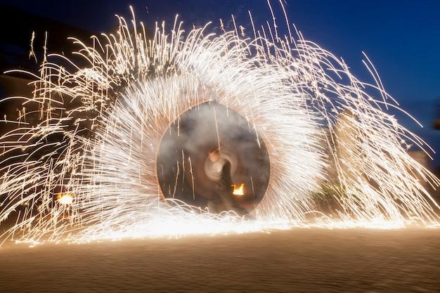 El hombre hace espectáculo con fuego chispeante