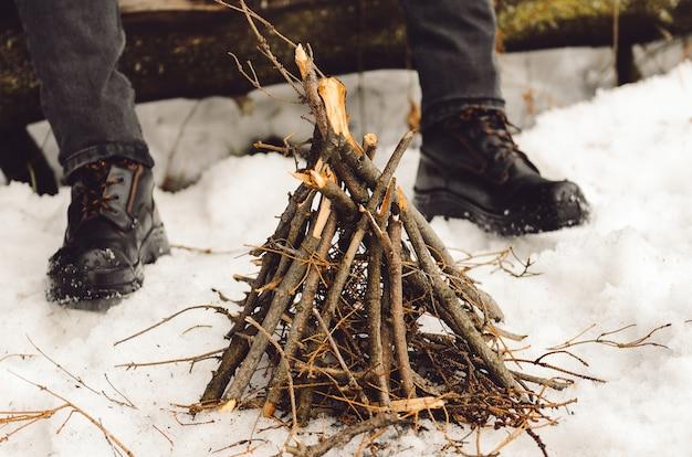 Un hombre hace una fogata en el invierno en una caminata.
