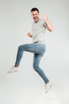 El hombre hace gesto ganador y saltando.