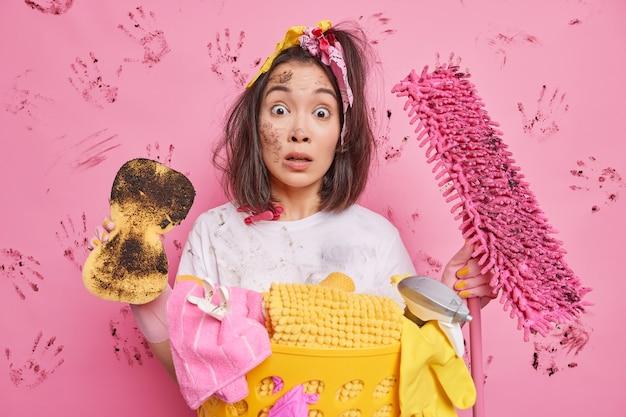 El hombre hace limpieza de la casa frota el polvo con una esponja sostiene herramientas sucias sorprendido de tener muchas poses de trabajo en la casa cerca de la canasta de lavandería en rosa