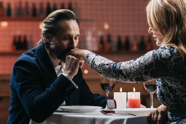 El hombre hace una propuesta de matrimonio y besa la mano de una mujer en un restaurante.