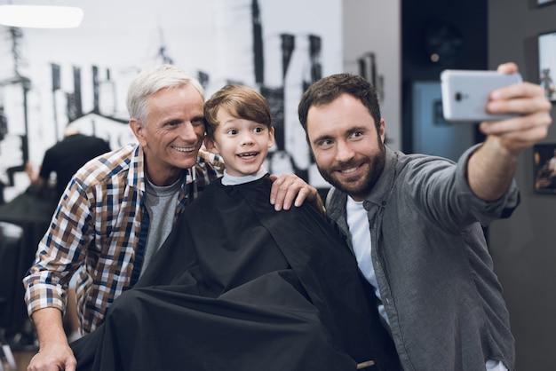 Hombre hace selfie en smartphone con hombre mayor y niño.
