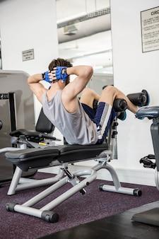 Hombre haciendo abdominales en el banco en el gimnasio