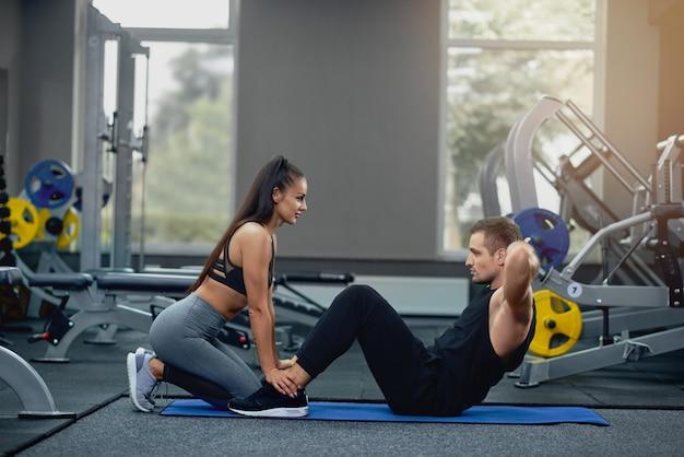 Hombre haciendo abdominales ejercicio de prensa con entrenador personal femenino.