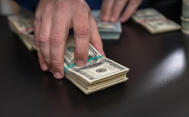 Hombre haciendo una apuesta, haciendo un pago u ofreciendo un soborno pasando por una gran pila de billetes de 100 dólares