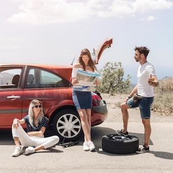 Hombre haciendo autostop con sus amigos después de un accidente automovilístico
