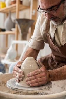 Hombre haciendo cerámica en interiores