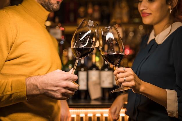 Hombre haciendo copas de vino con mujer