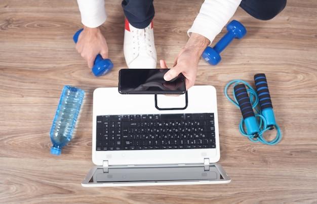 Hombre haciendo deporte en casa. ver entrenamiento en línea