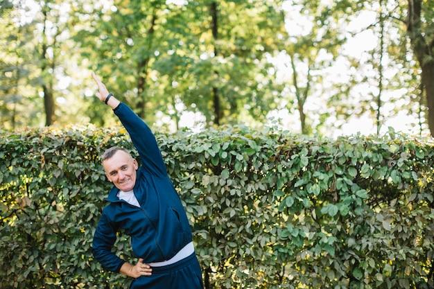 Hombre haciendo ejercicio al aire libre mientras sonríe a la cámara