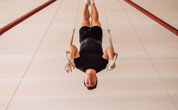 Hombre haciendo ejercicio en anillos de gimnasia